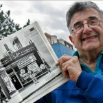 Larry Holding up Magazine Photo of Smith Pharmacy